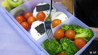 A fork being stuck into a lunch box full of broccoli, tomatoes, rice and eggs.