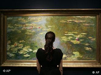 An auction house worker poses for the photographer in front of Claude Monet's Le bassin aux nympheas (1919)