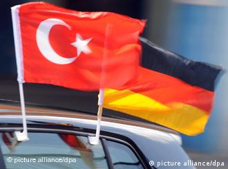 Turkish and German flags flying from a car window