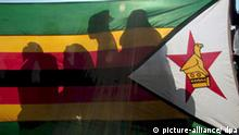 ZANU PF supporters wait behind the Zimbabwean flag for the address of Zimbabwe President Robert Mugabe at his last election runoff campaign rally in Chitungwiza, Zimbabwe, 26 June 2008. Mugabe used his final campaign speech to make a fresh offer to negotiate with the opposition MDC after the ballot. EPA/STR (zu dpa-Korr.: Simbabwer werden zur Wahl zwischen Mugabe und Mugabe geprügelt vom 26.06.2008) +++(c) dpa - Report+++