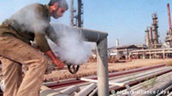 An Iraqi man working on an oil pipe