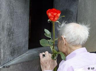 An old man, holding a rose, looks inside the memorial to gay nazi victims