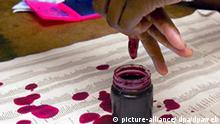 A Zimbabwean voter gets her finger dipped in purple dye to prove that she has voted and unable to vote a second time during the Zimbabwe Parlimentary Elections, Harare, Zimbabwe, Thursday 31 March 2005. EPA/STR +++(c) dpa - Report+++