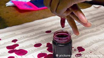 A Zimbabwean voter's finger being dipped in purple dye to prove that she has voted EPA/STR +++(c) dpa