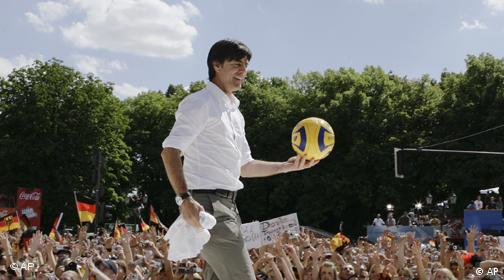 Germany's soccer team head coach Joachim Loew celebrates with fans at a public viewing zone in central Berlin