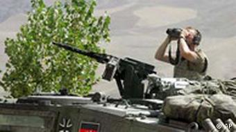 A German soldier sitting atop of a tank watches the area around Faisabad Airport in Afghanistan