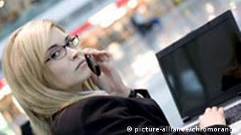 A woman with a laptop talking on a cell phone at an airport