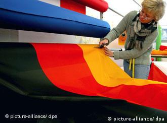 A woman cuts cloth in the colors of the German national flag