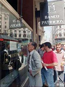 Customers of the Banco Patricios read a notice in a window of the bank in downtown Buenos Aires, Thursday, March 19, 1998. Banco Patricios announced that the Central Bank will suspended all banking activities for 30 days due a steep decline in deposits. The suspension means depositors will be unable to withdraw their funds, or carry out other transactions during the 30-day period. (AP Photo/Daniel Muzio)