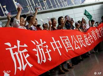 Pudong Flughafen Schanghai China Taiwan Flug Chinese passengers for the first regular weekend charter flights between China and Taiwan with a banner to photograph themselves at Pudong International Airport in Shanghai, China, on Friday July 4, 2008. The first regular weekend charter flights between the Chinese mainland and Taiwan began Friday. The historic step is aimed at warming relations between the self-ruled island of 23 million people and the mainland, which claims the island as its territory. (AP Photo/Eugene Hoshiko)