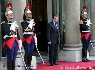 Sarkozy stands outside the Elysee Palace with three ceremonial guards