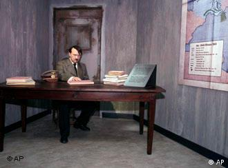 The wax figure of Adolf Hitler sitting behind a desk in a bunker scene