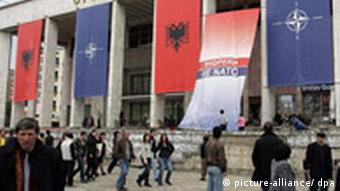 People standing beneath red and blue banners at a NATO conference