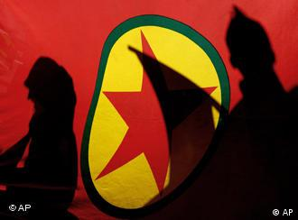 Kurdish demonstrators are silhouetted by a Kurdistan Workers' Party (PKK) flag