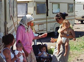 Roma women and children stand in from of a caravan
