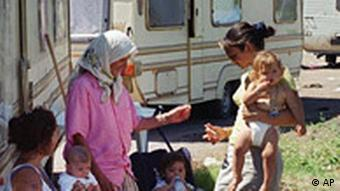 Roma and their babies sit outside their trailer homes in a temporary camp set up at Pomezia, near Rome, in July 2000