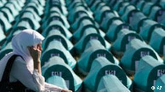 A Bosnian Muslim women weeps among coffins of Srebrenica victims