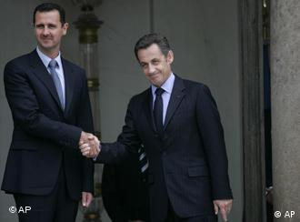 French President Nicolas Sarkozy, right, shakes hands with Syrian President Bashar Assad, left