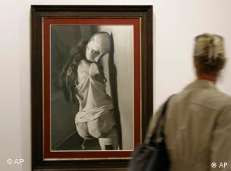 A woman passes the photo Die Puppe (The Doll) by artist Hans Bellmer