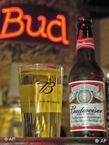 Glass filled with beer next to a Budweiser bottle. The shortened version of the Budweiser name called Bud is in neon red in the background.