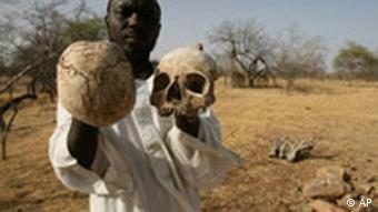 A Sudanese Darfur survivor holds human skulls at the site of a mass grave where he says the remains of 25 fellow villagers lie