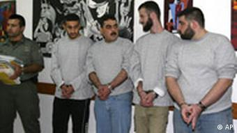 Four handcuffed Lebanese prisoners are seen with an Israeli prison official