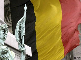 A tattered Belgian flag blowing in the wind at the Cinquantenaire monument in Brussels