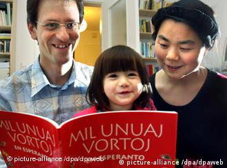 Matthias Ulrich and his wife Ms. Wang Nan Matthias read a children's book in Esperanto, with the title Mil Unuaj Vortoj (thousand first words), with their two year old daughter Christina in their home in Wiesbaden, a children's book in Esperanto, with the title Mil Unuaj Vortoj (thousand first words)