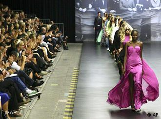 Women walking along runway platform as a row of audience members claps