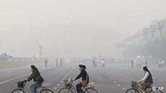 Chinese cycle through smog and pollution over Beijing's Tiananmen Square