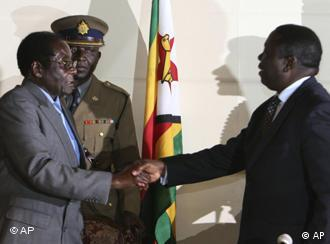 President Robert Mugabe, left shakes the hands of Morgan Tsvangirai, leader of the main opposition leader in Zimbabwe at the signing of a memorandum of understanding between the two parties in Harare