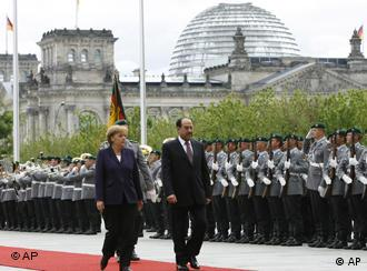 German Chancellor Angela Merkel, left, and Iraq's Prime Minister Nouri al-Maliki, right, review the honor guards during the welcoming ceremony prior to talks at the chancellery in Berlin, Tuesday, July 22