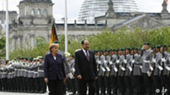 German Chancellor Angela Merkel, left, and Iraq's Prime Minister Nouri al-Maliki, right, review the honor guards during the welcoming ceremony prior to talks at the chancellery in Berlin, Tuesday, July 22, 2008.