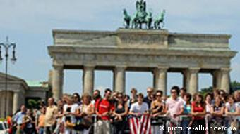 Crowds with some people carrying US flag in front of Berlin's Brandenburg Gate during Obama visit