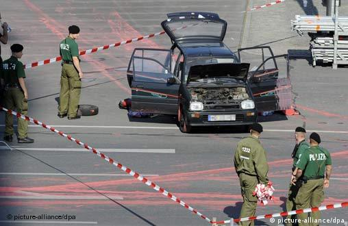 Police surround a car with red paint on the street
