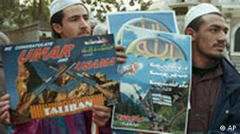 Activists of Islamic militant group sell posters outside the central mosque in Lahore.