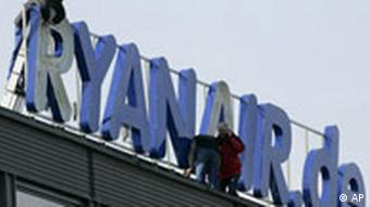 Workers fixing the Ryanair logo on the roof of the airport in Bremen, Germany