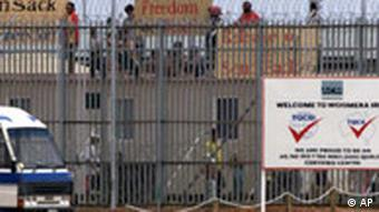 Asylum seekers holding signs stand on the refugee detention center's roof in protest in Woomera in Australia's Outback on Australia Day, Saturday, Jan. 26, 2002. About 200 refugees, some armed with iron bars, clambered onto roofs of huts at the camp in the Australian Outback and began chanting visa, visa and holding signs saying Freedom or death. A refugee was hospitalized after getting caught in barbed wire during the attempted mass breakout at the detention center. (AP Photo)