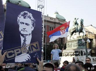 Supporters of ex-Bosnian Serb war crimes suspect Radovan Karadzic hold up pictures of him, during a protest in Belgrade, Serbia, Monday, July 28, 2008