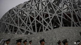 Chinese police officers march in front of the Olympic Stadium in Beijing.