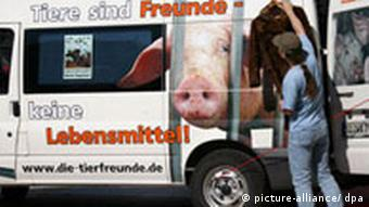 A truck showing a picture of a pig that says animals are friends, not food.