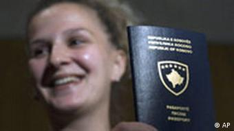A Kosovo Albanian woman shows her new Kosovo passport
