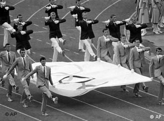 Suited Soviet youth march with the Olympic banner while others are carrying pigeons to be released, during opening ceremonies of the XXII Summer Olympic Games, July 19, 1980 in Moscow, Soviet Union.(