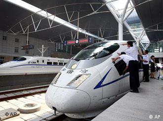 Chinese railway employees cleans the new high-speed CRH3 train as its arrived at the Tianjin Railway Station, China, during a trial run on the new Beijing-Tianjin line, Tuesday, July 22, 2008. A new high speed train link between Beijing and Tianjin, where Olympic soccer matches will be played, is scheduled to open on Aug 1. The train, which can run at speeds up to 350 kph, will cut the travel time between the two Olympic cities from 1 hour, 10 minutes to 25-30 minutes. (AP Photo/Andy Wong)