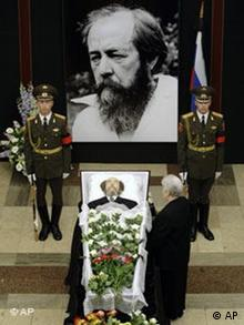 Alexander Solzhenitsyn's widow Natalya stands next to his coffin, during a farewell ceremony in Moscow on Tuesday, Aug. 5, 2008. Hundreds of Russians lined up in the pelting rain Tuesday to pay tribute to the author, who died Sunday at the age of 89, as the author, dissident and patriot lay in state inside the Russian Academy of Sciences. A military honor guard stood next to Solzhenitsyn's open casket, located in a cavernous hall at the academy, as mourners filed by and placed long-stemmed flowers at the foot of the bier. The ceremony had many of the trappings of a state funeral. Solzhenitsyn, who died from a chronic heart condition at his home outside Moscow, is to be buried at Moscow's Donskoi Monastery on Wednesday. (AP Photo/ Misha Japaridze)