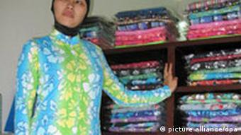 A woman wearing a bright blue and green burkini body robe stands in a small shop in front of a row of shelves holding other colorful body robes folded atop one another. +++(c) dpa - Report+++