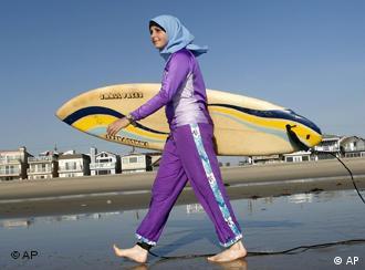 A woman walks along the sand dressed in swimwear designed for Muslim women