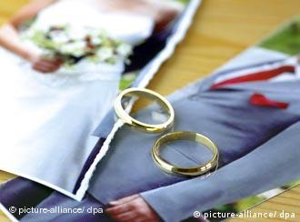 Symbolic picture of a wedding photograph torn in two with two gold wedding bands on top