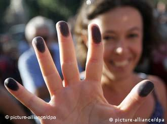 A woman with ink on her fingers protests a proposal to conduct a census of Roma in and near Rome