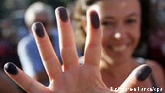 A woman with inked fingertips during a protest in Italy